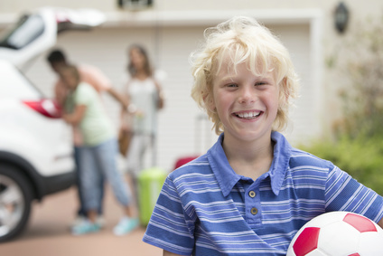 Portrait of smiling boy holding soccer ball in driveway